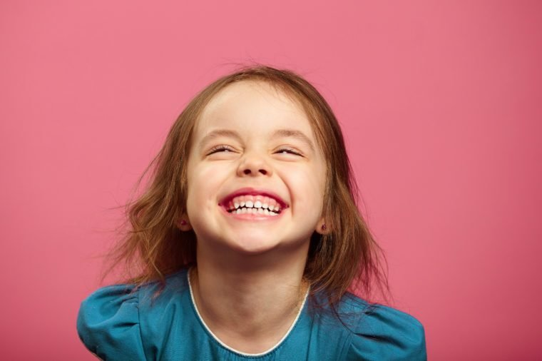 Joyful little girl sincere laughing at pink isolated background.