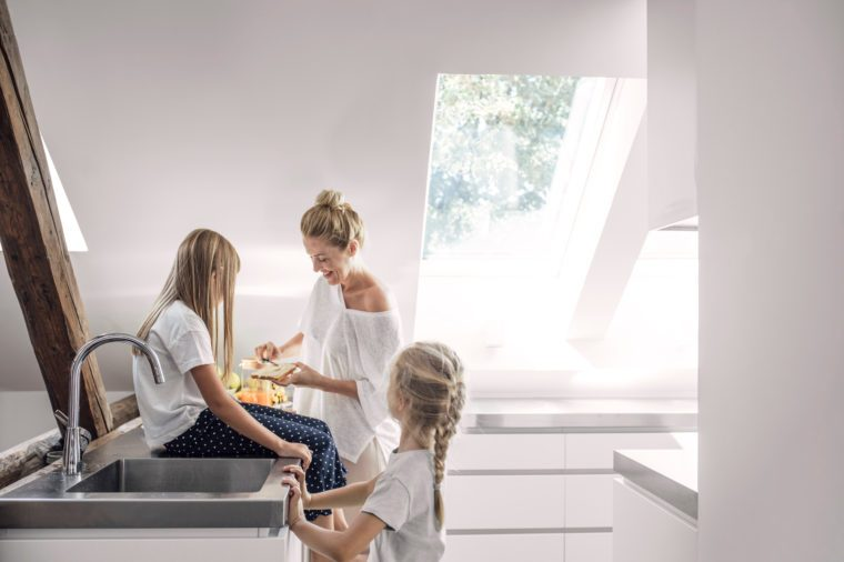 Pretty Caucasian smiling woman enjoying morning meal in kitchen with her cute daughters.