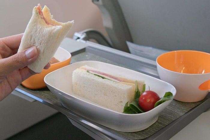 Woman eating sandwich on plane
