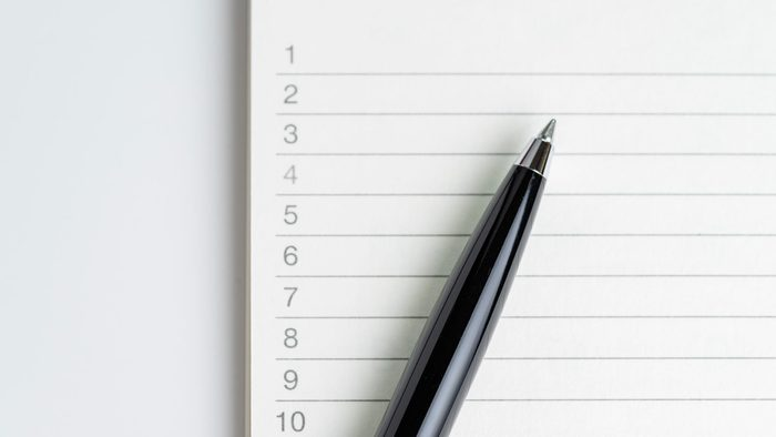 Close-up of pen on empty note paper sheet, white note pad with number listed priority or to do tasks.
