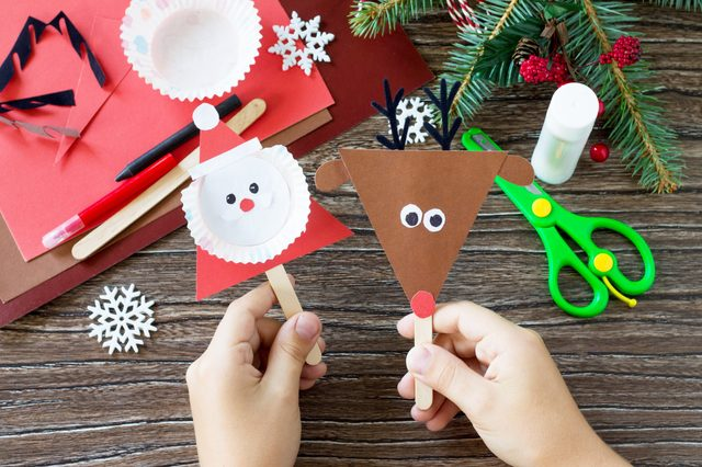 A child is holding Christmas Santa and Reindeer stics puppets. Handmade. Project of children's creativity, handicrafts, crafts for kids.