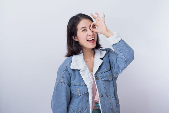 Caucasian smiling woman showing her hand with ok sign, Positive happy young asian girl wearing blue casual clothes portrait in studio