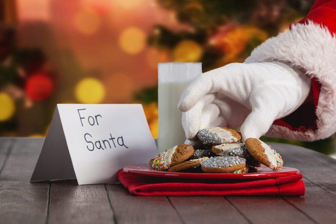 Digital composite of Santa eating cookies and milk at Christmas