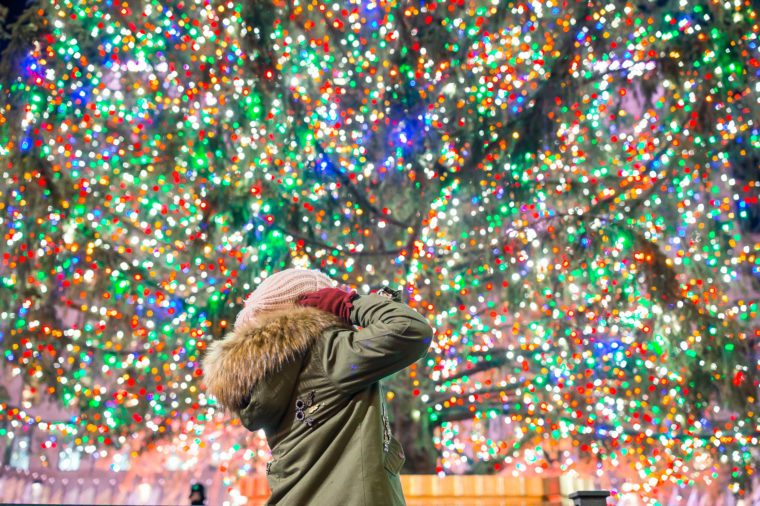 Happy girl on the background of the Rockefeller Christmas tree in New York. Beautiful Christmas Tree at Rockefeller center