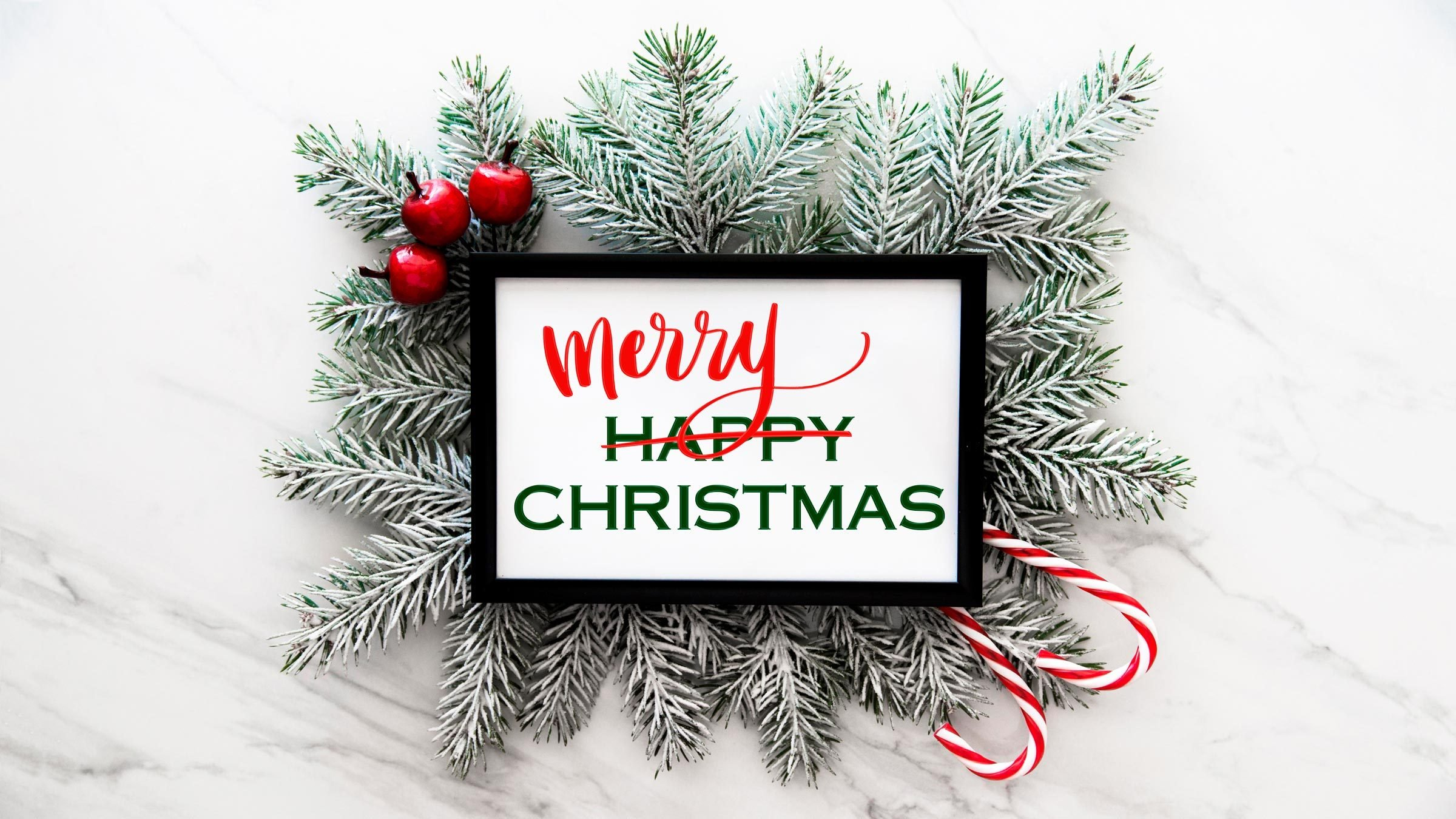 "fir tree branches on a marble background with framed white rectangle with text. text reads ""happy chirstmas"" with ""happy"" crossed out and ""merry"" written above"