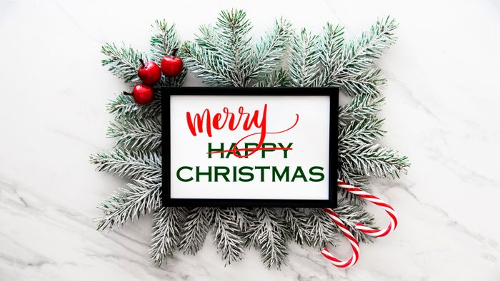 """fir tree branches on a marble background with framed white rectangle with text. text reads """"happy chirstmas"""" with """"happy"""" crossed out and """"merry"""" written above"""