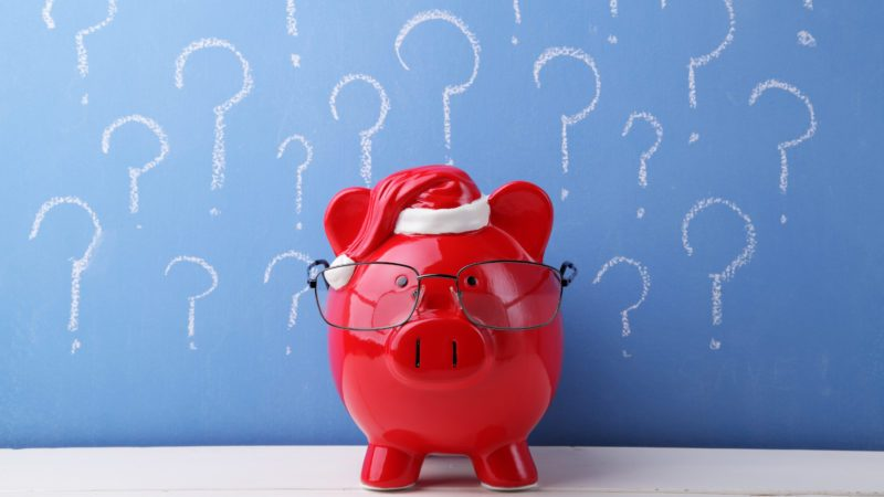 Red piggy bank with glasses in front of a blue chalkboard full of question marks