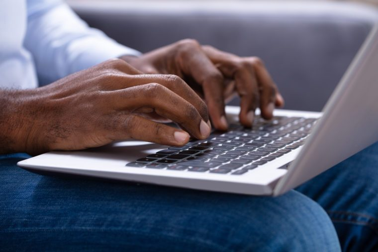 Close-up Of A Man's Hand Working On Laptop