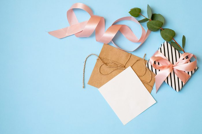 Bouquet of flowers, gift box, ribbon, craft envelope, blank greeting card on blue background with copy space for your text. Woman's day, 8 march, wedding, dating, love concept. Flat lay, top view.