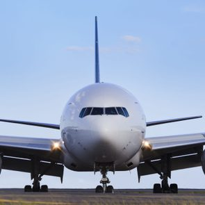 airplane front close-up view airfield ground day time blue sky clear background