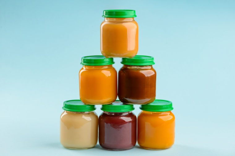 Jars of puree stacked pyramid on blue background. Different tastes of baby food: plum, pumpkin, carrot and banana.