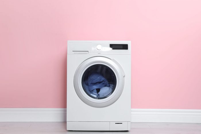 Washing machine with laundry near color wall. Space for text