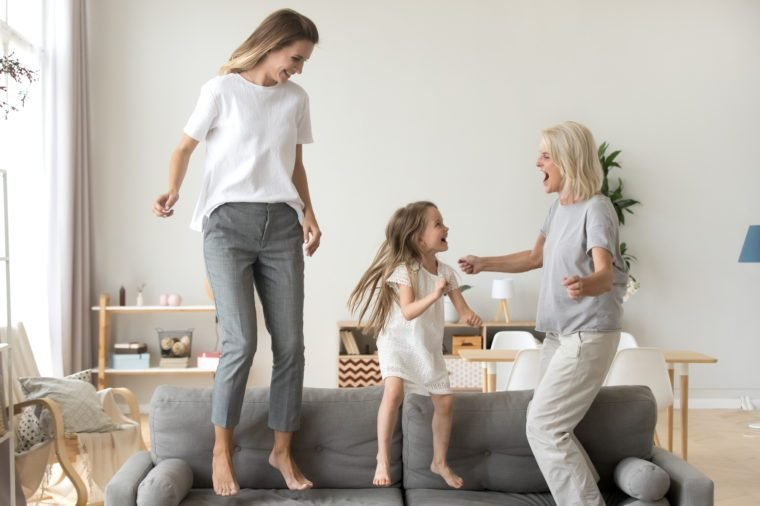 Happy kid granddaughter, mother and grandmother having fun jumping on sofa, cheerful three generations women family dancing in living room, grandma, mom and child laughing spending time together