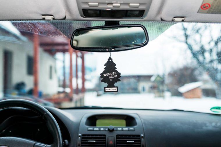 Hanging Black Classic Wunder Baum air freshener on car interior.