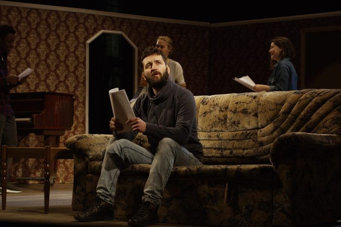 Medium shot of an actor reciting his lines on a sofa while other actors rehearsing in the background
