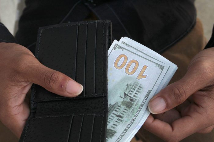 a man pulls cash from his wallet that shows one hundred dollar bill.
