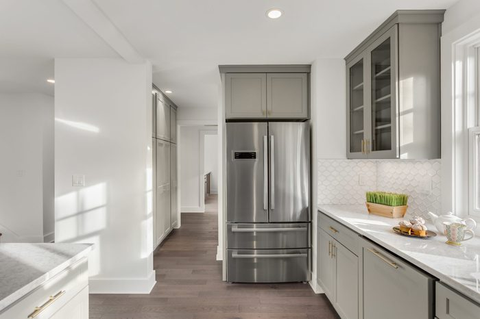 Kitchen Detail in Newly Remodeled Home: Hardwood Floors, Stainless Steel Refrigerator, and Quartz Counters