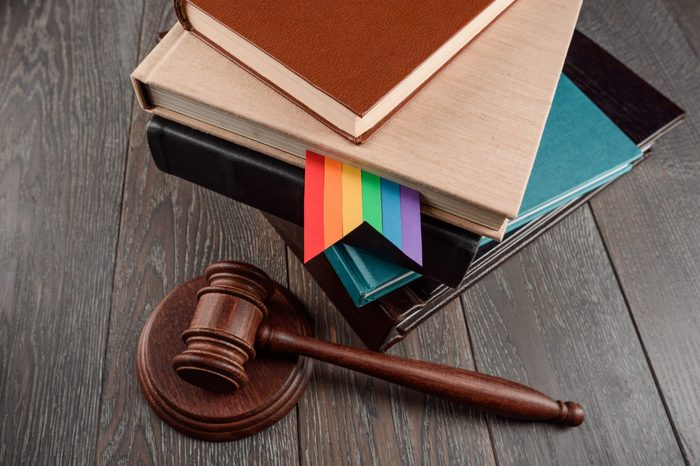Judge's gavel and books with a gay rainbow bookmark on wood table. LGBT rights, justice and law equality concept.