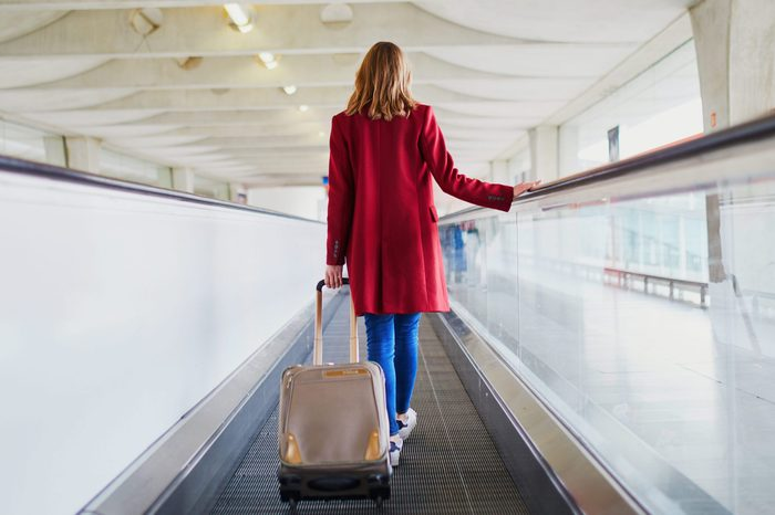 Young woman in international airport with luggage on travelator