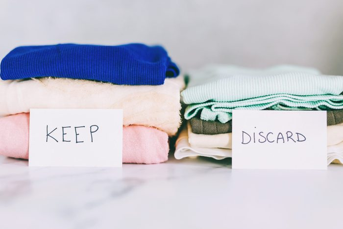 decluttering and tidying up concept: piles of tshirts and clothes being sorted into Keep Discard and Donate categories; Shutterstock ID 1337893610; Job (TFH, TOH, RD, BNB, CWM, CM): RD