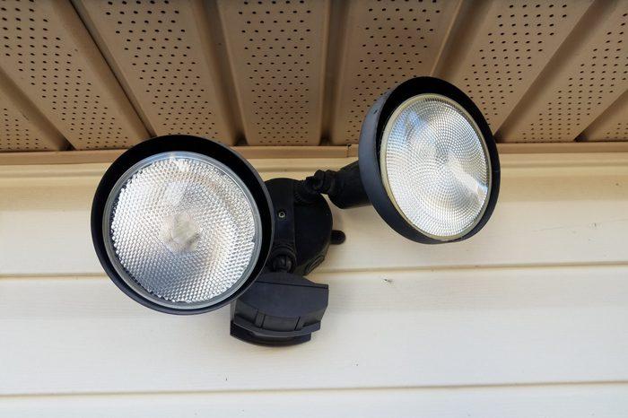 motion sensor flood light on white home siding
