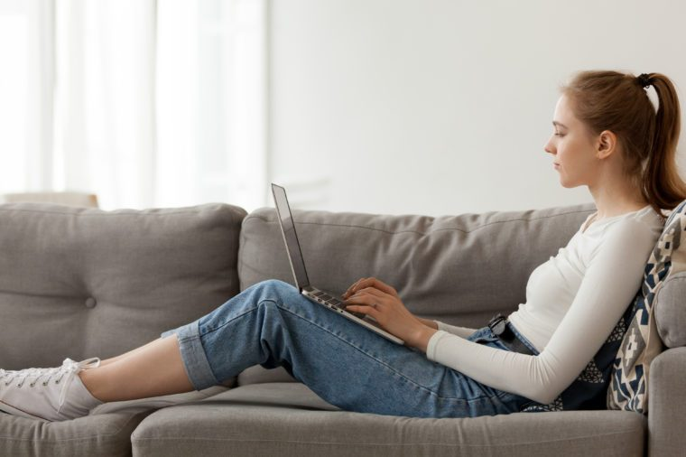Relaxing woman using laptop in living room, working on online project, internet shopping, sitting on comfortable sofa, reading email, chatting in social network, looking at screen, typing
