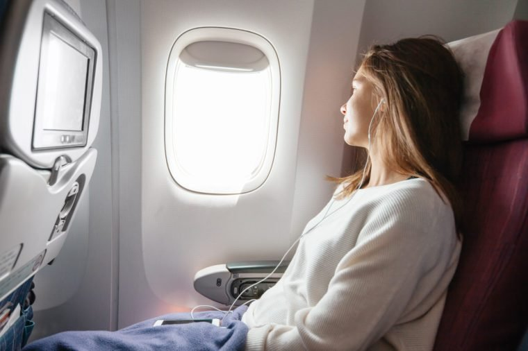 Teenage girl looking at plane window during flight. Young passenger travelling by airplane by first time.