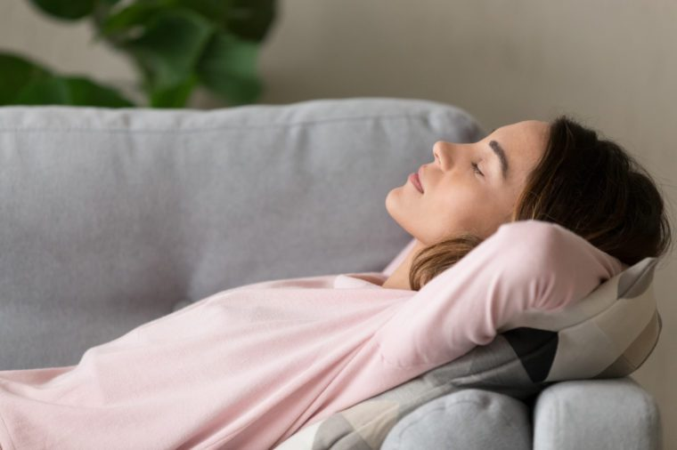 Side close up view young serene woman lying on comfy couch putting hands behind head closed her eyes sleeping or having day nap resting alone, lazy weekend at home refreshment and renew energy concept