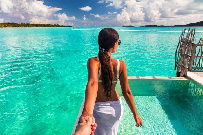 Follow me beach couple man holding girlfriend hand following woman to the swimming pool blue ocean vacation in Bora Bora, Tahiti ,French Polynesia.