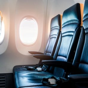 Plane interior - cabin with modern leather chair for passenger of airplane. Aircraft seats and window. - Horizontal image