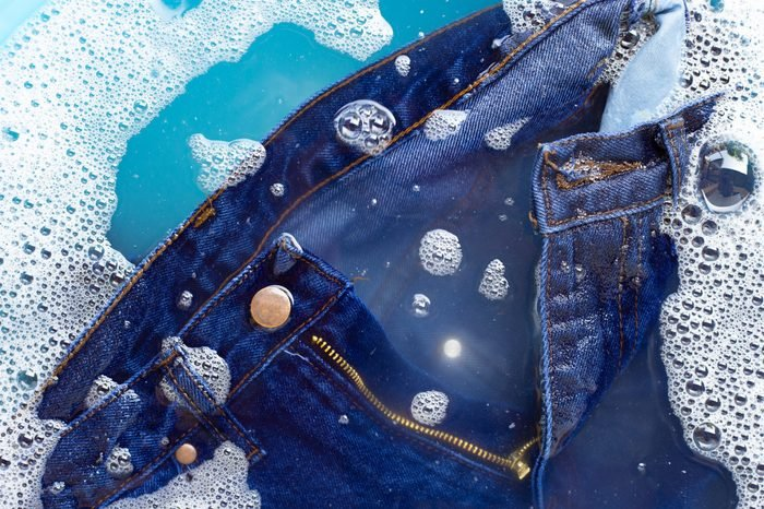 Jeans soak in powder detergent water dissolution, washing cloth. Laundry concept