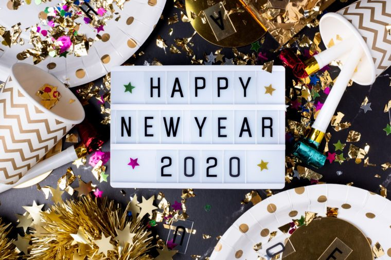 Happy new year 2020 table with modern light box with party cup,party blower,tinsel,confetti.Fun Celebration holiday party time table flat lay invitation or greeting card.new year eve concept