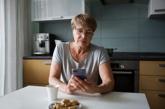 Portret happy senior woman looking at screen of mobile phone while in kitchen