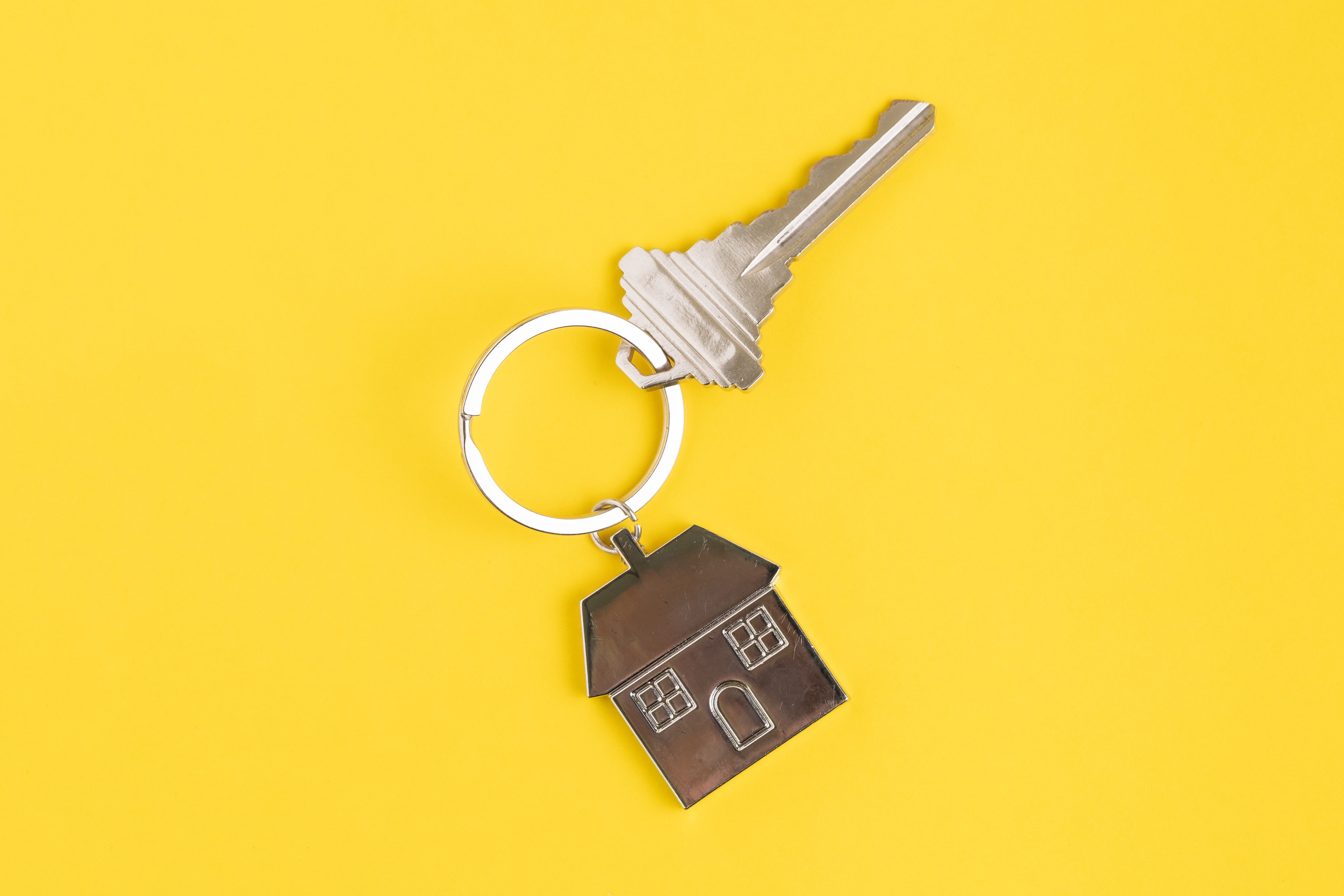 Home key with house keyring or keychain on solid yellow background using as home ownership, mortgage or buy and sell property and real estate.; Shutterstock ID 1478922593; Job (TFH, TOH, RD, BNB, CWM, CM): -