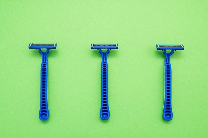 New disposable razor blade, on green background, isolated