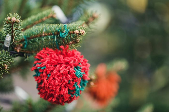 Wool handmade decoration on a Christmas tree outdoor. Diy yarn crafts creative ideas for children. Environment, recycle and zero waste concept. Selective focus, copyspace.