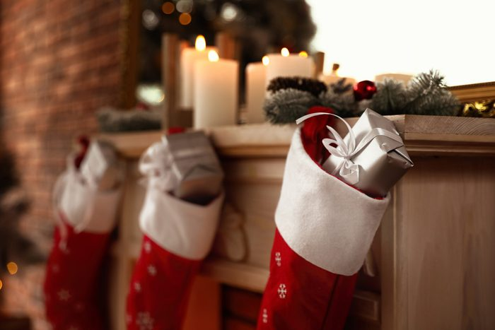 Decorative fireplace with Christmas stocking and gifts in stylish room interior