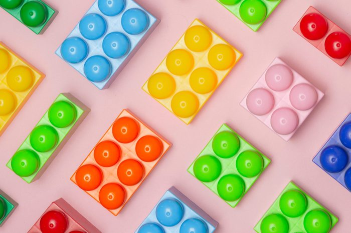 Colored toy bricks on a pink background with place for your content
