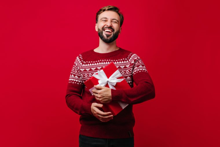 Laughing glad man with beard holding new year present. Studio portrait of white guy enjoying christmas.