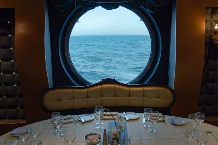 A served table in a restaurant against the backdrop of a huge round window on a cruise ship.