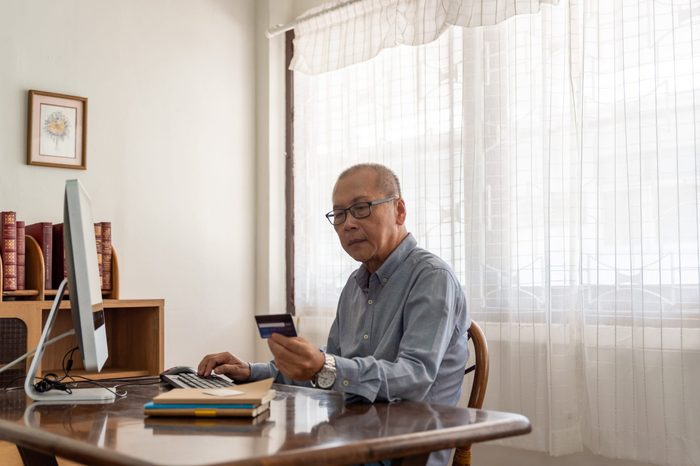 Senior man shopping online using computer and credit card.