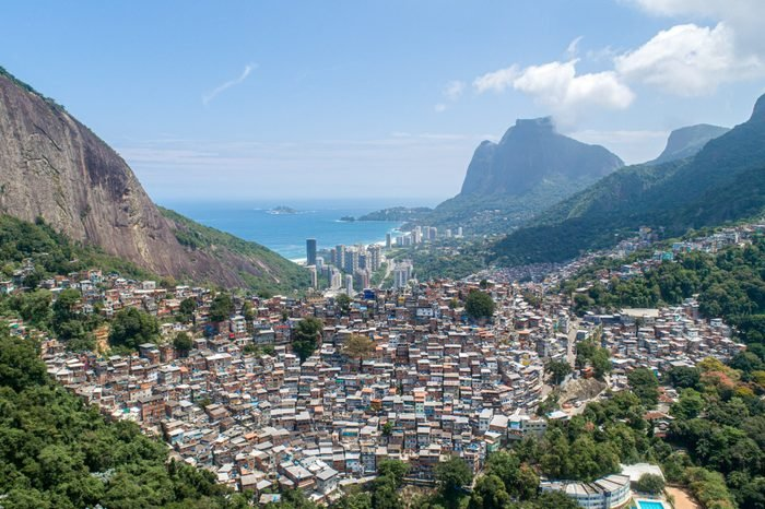 Aerial view of Favela da Rocinha, Biggest Slum in Brazil on the Mountain in Rio de Janeiro, and Skyline of the City behind