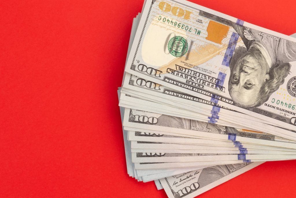 United States or USA dollar currency on a red background. Money for Christmas concept.