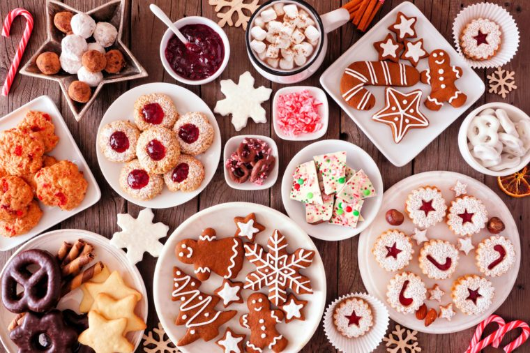 Christmas table scene of assorted sweets and cookies. Top view over a rustic wood background. Holiday baking concept.