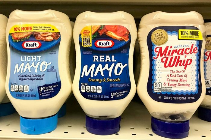 Several bottles of kraft mayonnaise on shelve at a grocery store