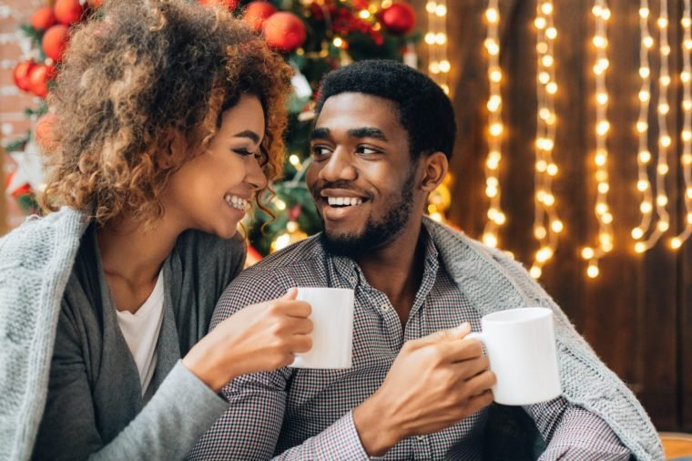 Happy young black couple drinking coffee and enjoying Christmas morning together, copy space