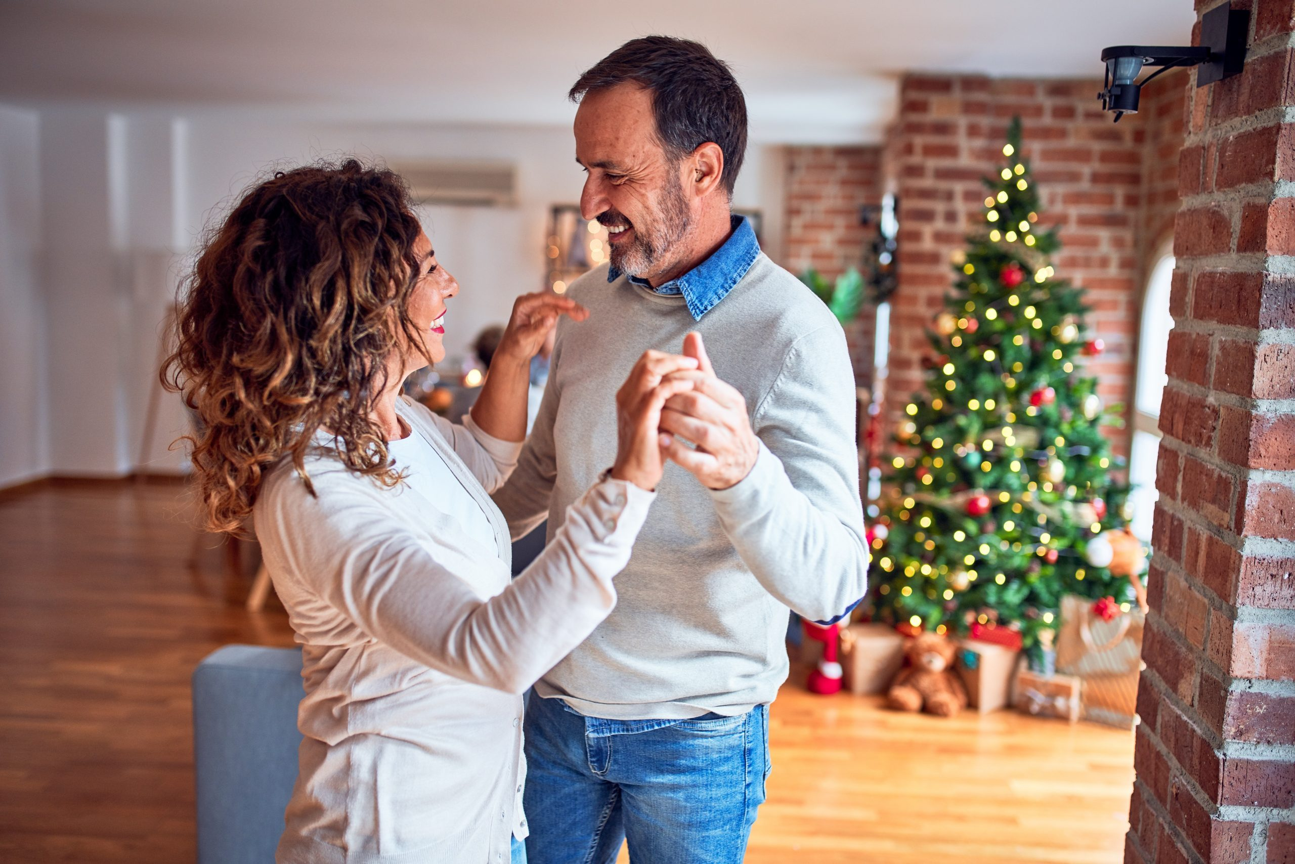 Middle age beautiful couple smiling happy and confident. Standing and dancing around christmas tree at home