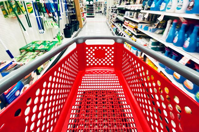 San Jose, CA - November 24, 2019: Motion blurred store shelves with wide view of the Target store red shopping cart in the center of the aisle.