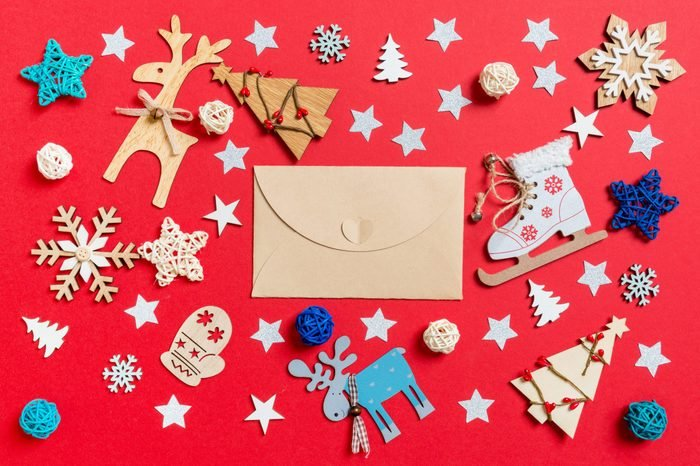 Top view of craft envelope, holiday toys and decorations on red Christmas background. New Year time concept.