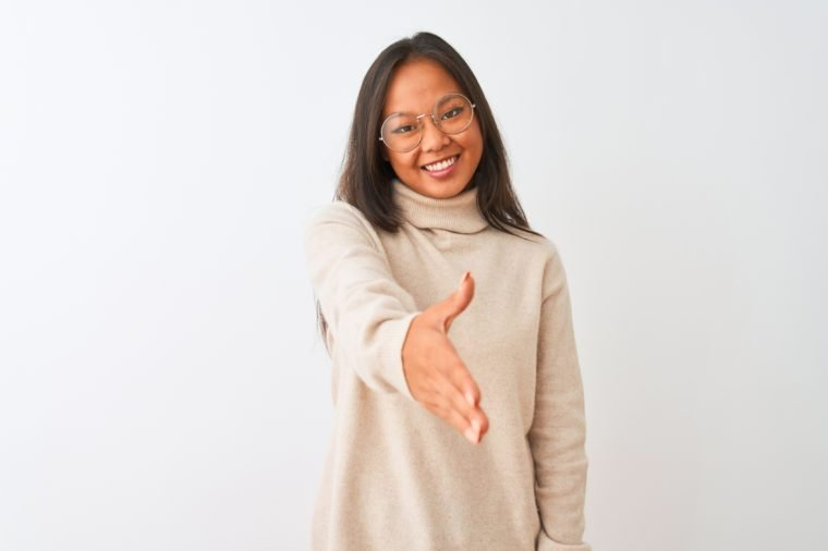 Young chinese woman wearing turtleneck sweater and glasses over isolated white background smiling friendly offering handshake as greeting and welcoming. Successful business.